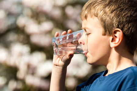 Photo pour Young boy drinking from glass of fresh water. Ideal for environmental protection or future generations concept. - image libre de droit
