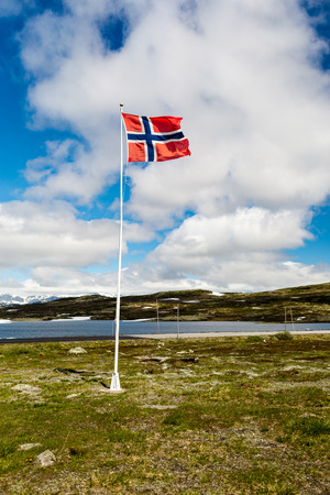 Norwegian flag on flagpole near the famous Hardangervidda plateau in western part of Norway.