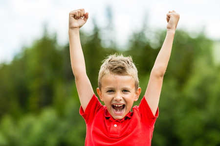 Photo for Self confident boy with raised fists celebrating a recent success or victory. - Royalty Free Image