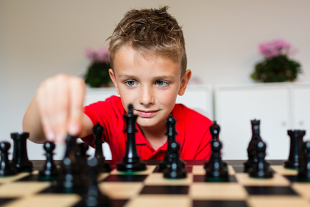 Photo pour Young white child playing a game of chess on large chess board. - image libre de droit