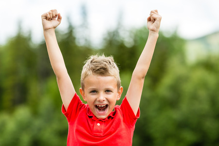 Photo pour Boy with raised arms and fists showing his excitement for recent success and high self esteem. - image libre de droit
