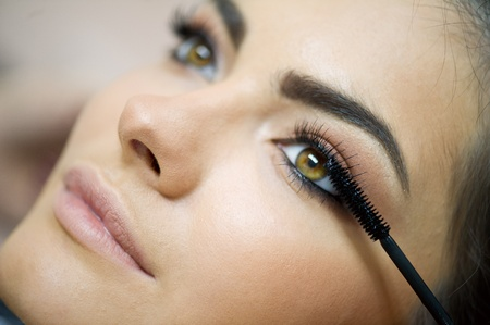 Woman applying mascara on her long eyelashes