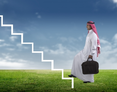 Photo pour arabian Businessman stepping up the stairs against a green scene  - image libre de droit