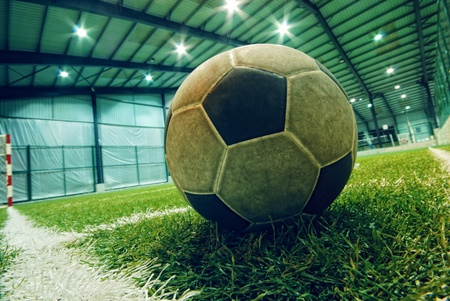 soccer ball on green grass in an indoor playground