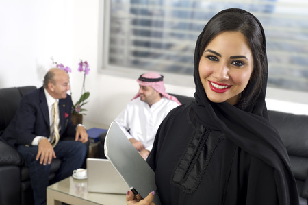 Photo pour Arabian Businesswoman in office with Businesspeople meeting in the background, Arabian woman wearing Hijab in office with her colleagues in background - image libre de droit