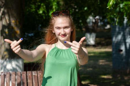 Foto für Cheerful girl making gun shot gesture. girl showing middle finger offensive gesture. Woman showing a fuck you off sign. negative expression Gesturing concept Portrait - Lizenzfreies Bild