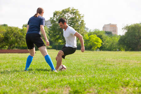 Photo pour Football player woman sliding tackle the ball from his opponent on football field at stadium Soccer - image libre de droit