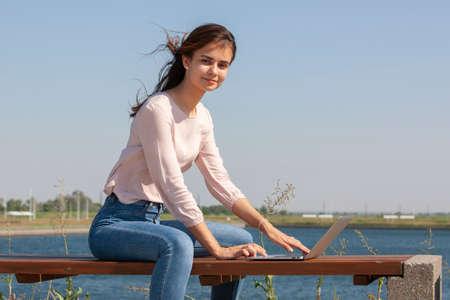 Photo pour Young woman with a laptop on a park bench. Portrait. - image libre de droit