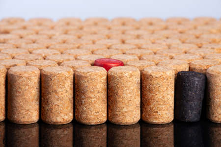 Photo pour Many identical corks for wine. Red and black corks stand out. The concept of tolerance, the fight against racism and homobobia. Close-up. - image libre de droit