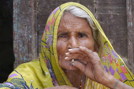 GWALIOR, INDIA - APRIL 15, 2016: An unidentified indian old women sitting and smoking.