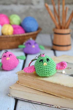 Foto de Colored crochet bird. The toy for babies or trinket. Handmade gift. DIY crafts concept. - Imagen libre de derechos