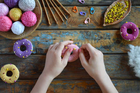 Photo for Making crochet amigurumi donuts. The toy for babies or trinket. On the table threads, needles, hook, cotton yarn. Handmade gift. DIY crafts concept. Step 2. Stuff the toy with padding polyester. - Royalty Free Image
