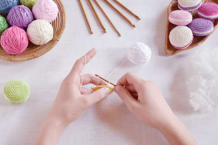 Photo pour Making crochet amigurumi french macarons. The toy for babies or trinket. Threads, needles, hook, cotton yarn. Handmade gift. Income from hobby. DIY crafts concept. Step 1 - knit all details. - image libre de droit