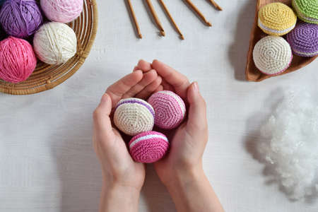 Photo for Making crochet amigurumi french macarons. The toy for babies or trinket. Threads, needles, hook, cotton yarn. Handmade gift. Income from hobby. DIY crafts concept. - Royalty Free Image