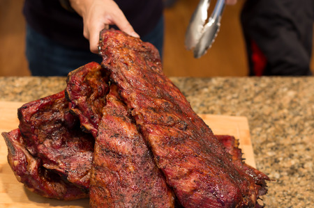 Man hand holding spare ribs on wooden board on family dinner time
