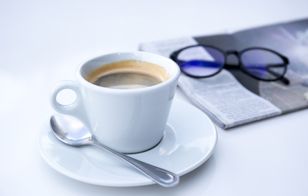 Fresh cup of coffee and news paper with glasses on white table
