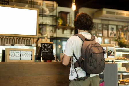 Traveler with rucksack waiting at counter in coffee shop