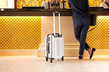 Foto de Woman tourist with suitcase chek in at reception hotel - Imagen libre de derechos