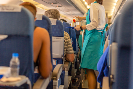 Photo pour Flight attendant serve drink to passengers on board. - image libre de droit