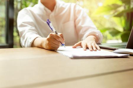 Photo pour Hand filling document form contract with laptop an mouse on wooden table. - image libre de droit