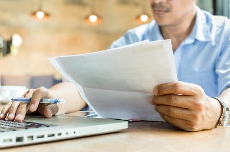 Photo pour Businessman hands holding document paperwork and pen working on laptop. - image libre de droit