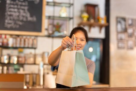 Photo for Waitress at counter giving eco friendly paper bag with take away drink in cafe. - Royalty Free Image
