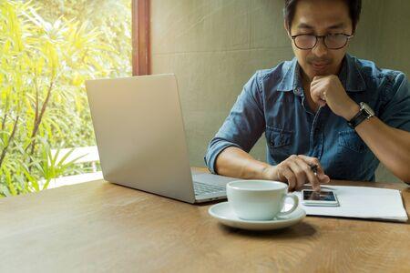 Foto de Businessman using cell phone with laptop and coffee cup on wooden desk. - Imagen libre de derechos