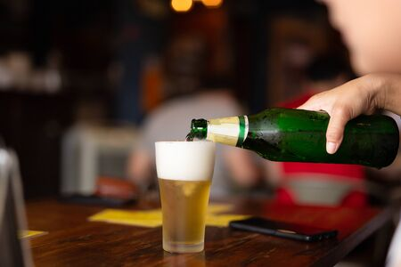 Photo pour Hand pouring beer from bottle into a glass in blur - image libre de droit