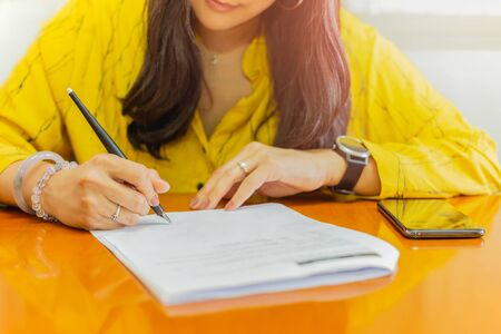 Photo pour Businesswoman signing contract document paper on wood table. - image libre de droit
