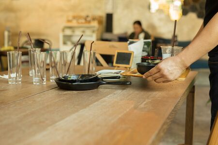 Photo pour Waiter hand holding tray with dirty dishes in the restaurant - image libre de droit
