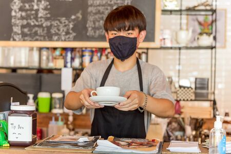 Photo pour Social distance conceptual small business waiter serving coffee to customer in cafe. - image libre de droit