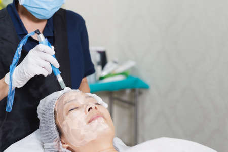 Photo for Woman having stimulating facial treatment at professional clinic. - Royalty Free Image