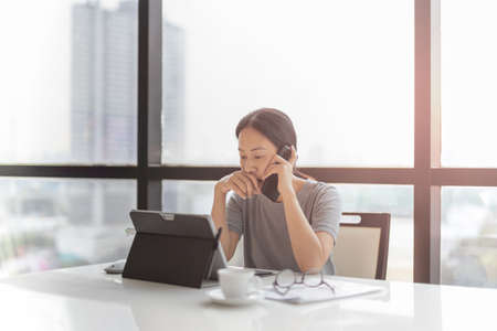 Photo pour Businesswoman talking on cell phone while working on laptop. - image libre de droit