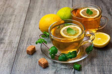 Photo pour Two Glass tea Cup's with lemon, lime and mint on gray wooden background. - image libre de droit