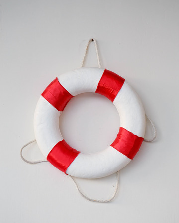 White Life buoy with a board on white wall