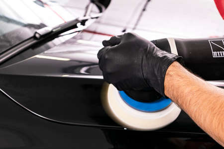 Photo pour Car polish wax worker hands applying protective tape before polishing. Buffing and polishing car. Car detailing. Man holds a polisher in the hand and polishes the car - image libre de droit