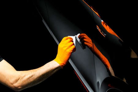 Foto de Car polish wax worker hands polishing car. Buffing and polishing vehicle with ceramic. Car detailing. Man holds a polisher in the hand and polishes the car with nano ceramic. Tools for polishing - Imagen libre de derechos