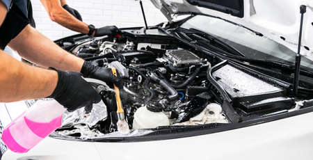 Photo pour A man cleaning car engine with shampoo and brush. Car detailing or valeting concept. Selective focus. Car detailing. Cleaning with sponge. Worker cleaning. Car wash concept solution to clean - image libre de droit