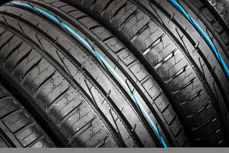 Photo for Studio shot of a set of summer car tire on black background. Tire stack background. Car tyre protector close up. Black rubber tire. Brand new car tires. Close up black tyre profile. Car tires in a row - Royalty Free Image