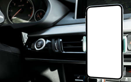 Photo for Smartphone in a car use for Navigate or GPS. Driving a car with Smartphone in holder. Mobile phone with isolated white screen. Blank empty screen. copy space. Empty space for text. modern car interior - Royalty Free Image