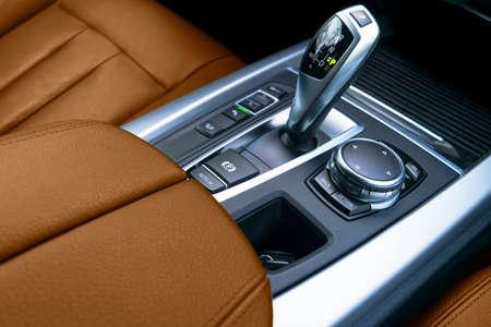 Photo pour Automatic gear stick (transmission) of a modern car. Multimedia and navigation control buttons. Car interior details. Transmission shift. Brown leather interior. - image libre de droit