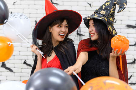 Foto de Portrait of beautiful young asian woman wearing witch costume holding pumpkin Jack O Lantern and balloon on background decorated for Halloween - Imagen libre de derechos