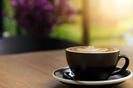 Photo pour Nice cup of fresh brewed coffee with beautiful latte art on wooden table in cafe with copy space. Coffee break recreation relaxation - image libre de droit