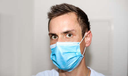 Photo pour young european man wearing blue medical face mask to protect against disease. covid-19 virus outbreak, white blurred background. health concept - image libre de droit