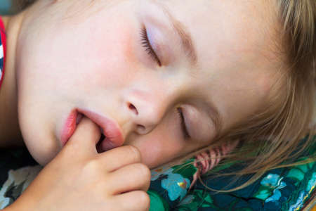 Photo for Little pretty girl sleeping, sucking thumb and having sweet dreams - Royalty Free Image
