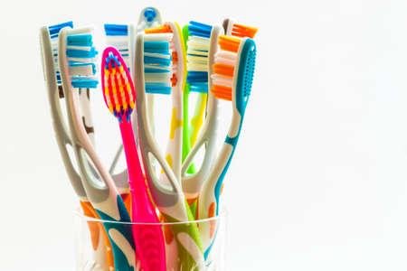 Foto de Close up shot of set of multicolored toothbrushes in glass on clean toilet on white background, concept dental. - Imagen libre de derechos