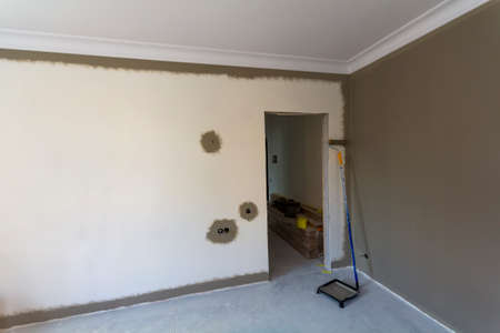 Interior of a apartement room during renovation work. Painting of the walls with dark paint.