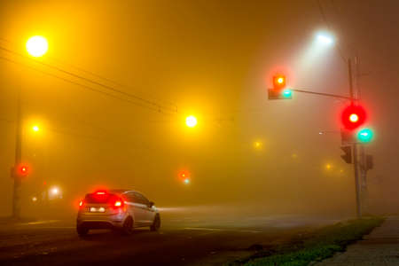 Thick fog over empty road with lonely car and traffic lights at night