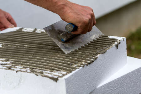 Foto de Close-up of worker hand with trowel applying glue on white rigid polyurethane foam sheet for house insulation. Modern technology, renovation, professional job, alternative for mineral wool concept. - Imagen libre de derechos