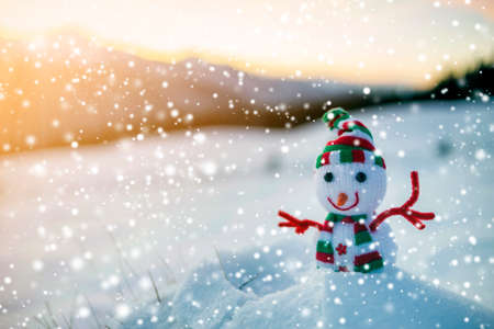 Photo for Small funny toy baby snowman in knitted hat and scarf in deep snow outdoor on blurred mountains landscape and falling big snowflakes background. Happy New Year and Merry Christmas greeting card theme. - Royalty Free Image